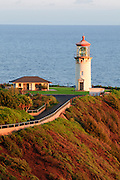 Kilauea Lighthouse on the island of Kauai, Hawaii as the early morning sun rises and lights it from the side.