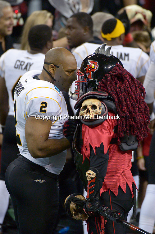 Orlando Predators mascot Klaw, right, meets with Pittsburgh Power linebacker James Bryant (2) before an AFL playoffs football game in Orlando, Fla., Sunday, Aug. 3, 2014. (Photo by Phelan M. Ebenhack)