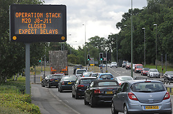 © Licensed to London News Pictures. 28/07/2015<br /> Operation Stack warning sign near junction 7 for Bearsted,Kent<br /> Operation stack is back on the M20 in Kent.<br /> Just days after Operation Stack was taken off the M20, it was brought back in the early hours of this morning.<br /> The authorities are blaming a heavy volume of traffic heading towards the Port of Dover and Eurotunnel and the continued disruption in Calais.<br /> The coast-bound carriageway between junctions 8 and 9 is closed to allow lorries to park, but the slip roads at junctions 9, 10 and 12 and 13 have also been shut. <br /> <br /> (Byline:Grant Falvey/LNP)
