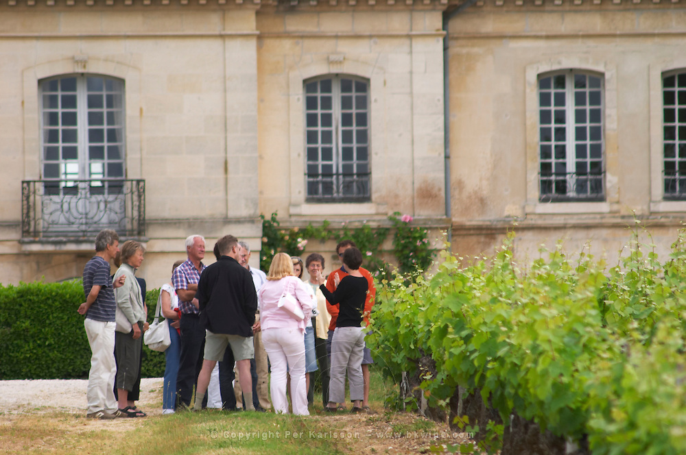 A group of visiting wine tasters in the vineyards with the guide gesticulating and the chateau building in the background Chateau Bouscaut Cru Classe Cadaujac Graves Pessac Leognan Bordeaux Gironde Aquitaine France