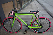 Colourful bicycle in flourescent yellow and with pink tyres in London, United Kingdom. While this is not a fixie or fixed wheel cycle, it does have similar styling to some of the hipster bikes around the capitay, where cycling has become increasingly about the style.