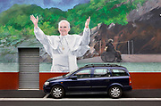 Car parked in front of a wall mural depicting a healing bath being blessed by Pope John Paul II , 22nd March 2008, Lourdes, France.<br /> Lourdes was originally a small market town lying in the foothills of the Pyrenees. Following the claims that there were apparitions of Our Lady of Lourdes to Bernadette Soubirous in 1858, Lourdes has developed into a major place of Christian pilgrimage. The spring water from the grotto is believed to possess healing properties, An estimated 200 million people have visited the shrine since 1860, and the Roman Catholic Church has officially recognized 67 miracle healings.
