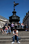 Tourists gather on a beautiful spring day around the famous statue of Eros at Piccadilly. Piccadilly Circus is a famous road junction and public space of London's West End in the City of Westminster, built in 1819 to connect Regent Street with the major shopping street of Piccadilly.