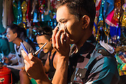 23 NOVEMBER 2013 - BANGKOK, THAILAND:  A cast member of the Prathom Bunteung Silp mor lam troupe puts on his makeup backstage during a performance in Bangkok. Mor Lam is a traditional Lao form of song in Laos and Isan (northeast Thailand). It is sometimes compared to American country music, song usually revolve around unrequited love, mor lam and the complexities of rural life. Mor Lam shows are an important part of festivals and fairs in rural Thailand. Mor lam has become very popular in Isan migrant communities in Bangkok. Once performed by bands and singers, live performances are now spectacles, involving several singers, a dance troupe and comedians. The dancers (or hang khreuang) in particular often wear fancy costumes, and singers go through several costume changes in the course of a performance. Prathom Bunteung Silp is one of the best known Mor Lam troupes in Thailand with more than 250 performers and a total crew of almost 300 people. The troupe has been performing for more 55 years. It forms every August and performs through June then breaks for the rainy season.              PHOTO BY JACK KURTZ