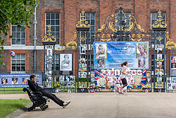 Licensed to London News Pictures. 01/07/2021. London, UK. Members of the public walk past the gates of Kensington Palace which have been decorated by Royal fans to mark what would have been Diana's 60 birthday. Today, HRH Prince William and Prince Harry will unveil a statue of their mother Diana Princess of Wales at Kennsington Palace in West London to mark her 60th birthday. Photo credit: Alex Lentati/LNP
