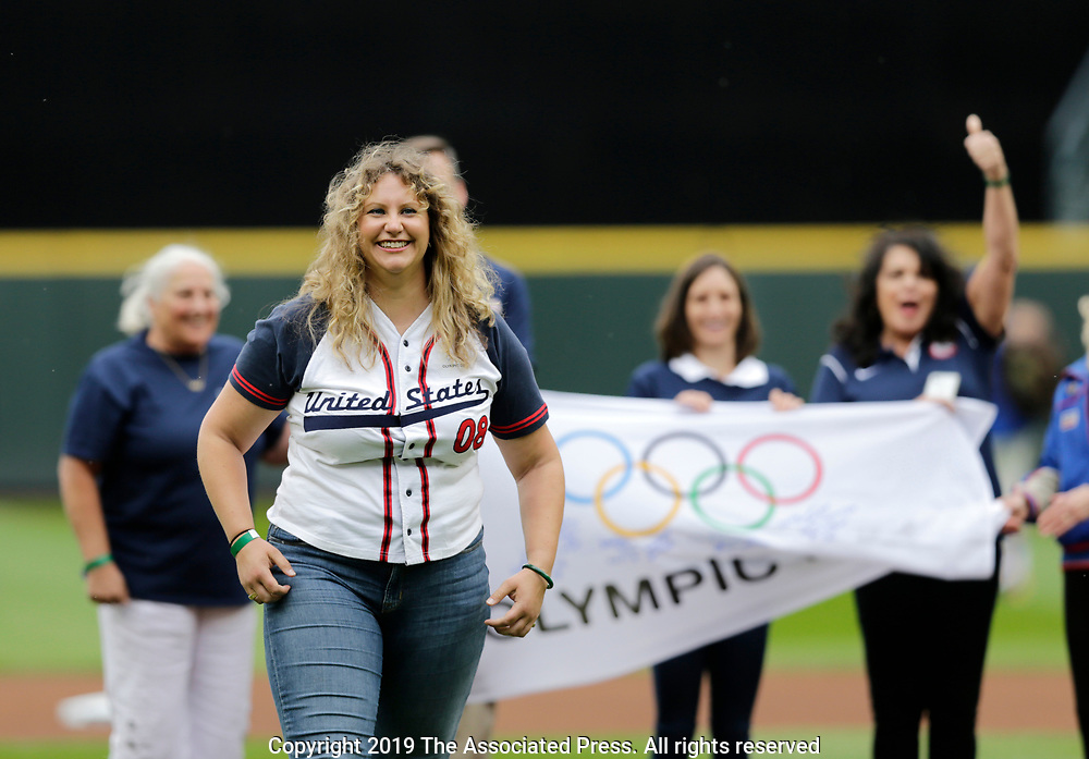 Former U.S. Olympic swimmer Margaret Hoelzer smiles after throwing out the first pitch before a baseball game between the Baltimore Orioles and the Seattle Mariners, Sunday, June 23, 2019, in Seattle. (AP Photo/John Froschauer)