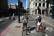 Two young women riding Santander bike hire cycles in London, England, United Kingdom. The scheme, sponsored by Santander is intended to get Londoners cycling. As part of a major initiative. These free for the first half hour bikes are then charged for how long you use them. Take a cycle, ride it where you like, then return it, ready for the next person. Available 24 hours a day, all year round. Its self-service and theres no booking.