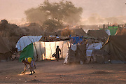 Sunrise at the Breidjing Refugee Camp in eastern Chad. Another day of waiting begins. It's November, two months after the rainy season but not yet the hot season. Smoke from cookfires chimneys up into the sky; women sweep the dirt in front of their tents; children walk to the water depot with empty plastic containers; roosters crow and donkeys bray into the desert air, which is beginning to lose its nighttime chill. Hungry Planet: What the World Eats (p. 58).