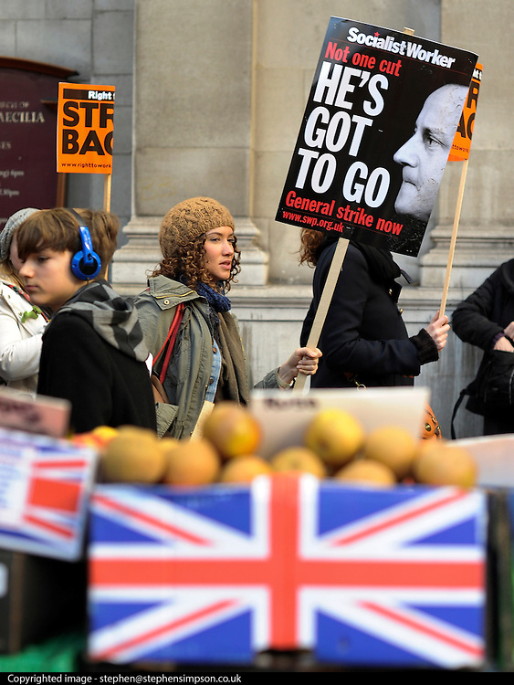 © Licensed to London News Pictures. 30/11/2011, London, UK. A woman carrying a banner calling for David Cameron to go walks past a vegetable stall. Up to two million public sector workers are staging a strike over pensions in what is set to be the biggest walkout for a generation. Photo credit : Stephen Simpson/LNP