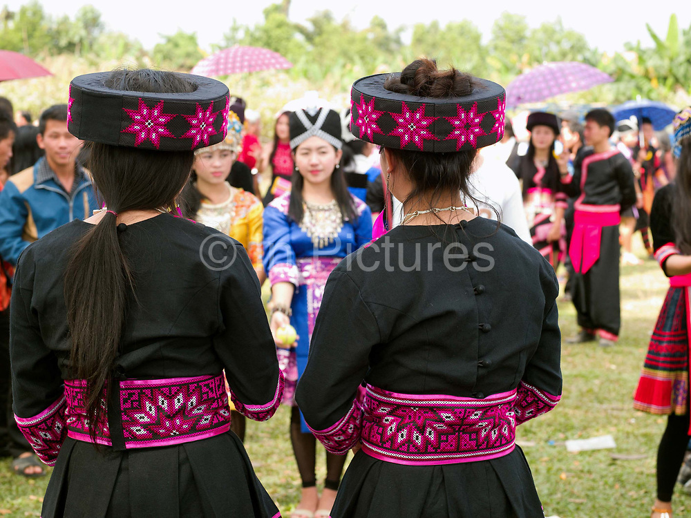 Hmong Der (White Hmong) women playing the ball throwing game of 'pov pob' at Ban Km 52 Hmong New Year festival, Vientiane province, Lao PDR. 'Pov pob' is a formalised courting ritual where unmarried men and women face each other in a line and toss cloth balls (or tennis balls) to one another using only one hand. The Hmong celebration of New Year is based on the lunar calendar. This important time is an opportunity to honour ancestors and spirits through offerings and rituals and to partake in games, sports, feasts, shows, bullfights and courtship. The Hmong are the third largest ethnic group in Laos. One of the most ethnically diverse countries in Southeast Asia, Laos has 49 officially recognised ethnic groups although there are many more self-identified and sub groups. These groups are distinguished by their own customs, beliefs and rituals.