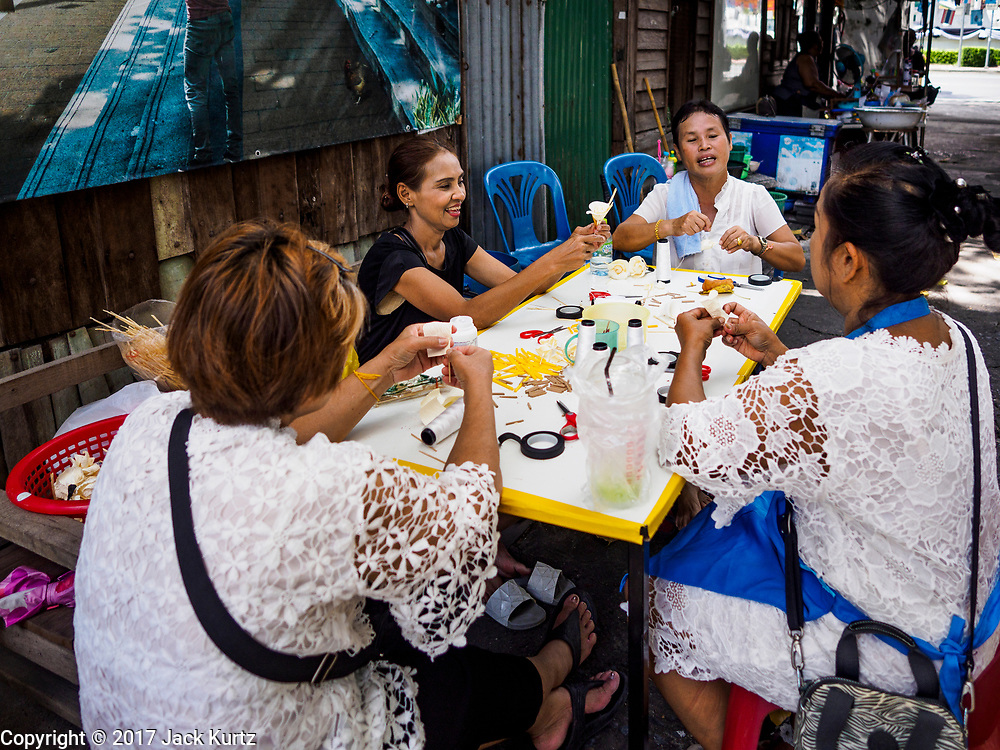 19 OCTOBER 2017 - BANGKOK, THAILAND: Women in Pom Mahakan slum make sandalwood flowers they will use as offerings during the royal cremation in Bangkok next week. Most of the people living in the slum have been evicted, and the land they were living on has been turned into a volunteer center for people helping with the royal cremation, which is October 25-29, 2017. After the cremation the land will be turned into a public park.     PHOTO BY JACK KURTZ