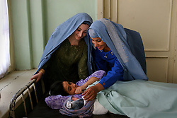 Shafika Abbasi, 20, left, who was living in Burke, Va. for the last four years and a relative, Belquis Azizyar, right, visits her cousin Nafisa Arifi after she gave birth to a baby girl  at the Rabia Balkhi hospital in Kabul, Afghanistan August 4, 2002. Infant mortality in Afghanistan in 2000 was 165 per 1,000. live births - one of the highest figures in the world, according to the United Nations International Children's Fund (UNICEF). More than one if four children die before age 5. The U.S. infant mortality rate is 7 per 1,000. Half Afghanistan's children suffer from malnutrition. (Photo  by Ami Vitale)