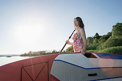 Mature woman carrying stand up paddle board at lakeshore, Bavaria, Germany