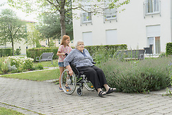 Senior woman on wheelchair with granddaughter at rest home park, Bavaria, Germany