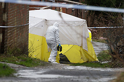 © Licensed to London News Pictures . 15/02/2014 . Oldham , UK . A man in a forensic suit carries a metal weight to the crime scene tent , as it blows in the wind . Police and crime scene investigators close off an alleyway behind terraces parallel to Ripponden Road this morning (15th February 2014) where it is reported the body of a fifteen year old boy - named locally as Leon Cudworth - was discovered in the early hours . Photo credit : Joel Goodman/LNP