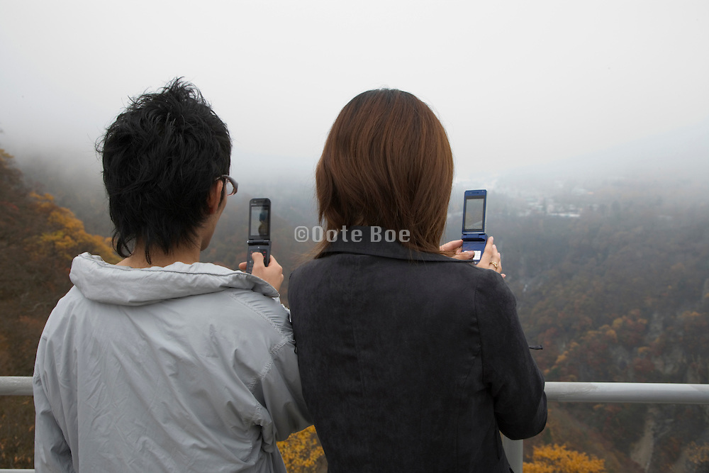 two people photographing with cellphones, Akechidaira observatory in foggy weather