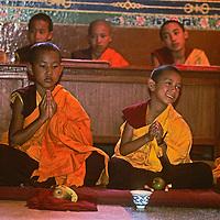 NEPAL, Kathmandu. Young Buddhist monks pray in new monastery near Bodh'nath.
