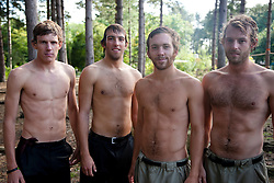Group of young men standing in a forest shirtless and wet