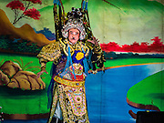 17 FEBRUARY 2016 - BANGKOK, THAILAND: A performer on stage during a Chinese opera performance at a small shrine in a residential part of Bangkok. The small troupe travels from Chinese shrine to Chinese shrine performing for a few nights before going to another shrine. They spend about half the year touring in Thailand and the other half of the year touring in Malaysia. Members of the troupe are paid about 5,000 Thai Baht per month (about $140 US). Chinese opera was once very popular in Thailand, where it is called Ngiew. It is usually performed in the Teochew language. Millions of Chinese emigrated to Thailand (then Siam) in the 18th and 19th centuries and brought their culture with them. Recently the popularity of ngiew has faded as people turn to performances of opera on DVD or movies. There are still as many 30 Chinese opera troupes left in Bangkok and its environs. They are especially busy during Chinese New Year and Chinese holiday when they travel from Chinese temple to Chinese temple performing on stages they put up in streets near the temple, sometimes sleeping on hammocks they sling under their stage. Most of the Chinese operas from Bangkok travel to Malaysia for Ghost Month, leaving just a few to perform in Bangkok.     PHOTO BY JACK KURTZ
