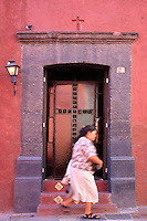 Woman passes door in San Miguel de Allende Mexico