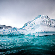 An iceberg with a large section under the water in Curtis Bay, Antarctica.