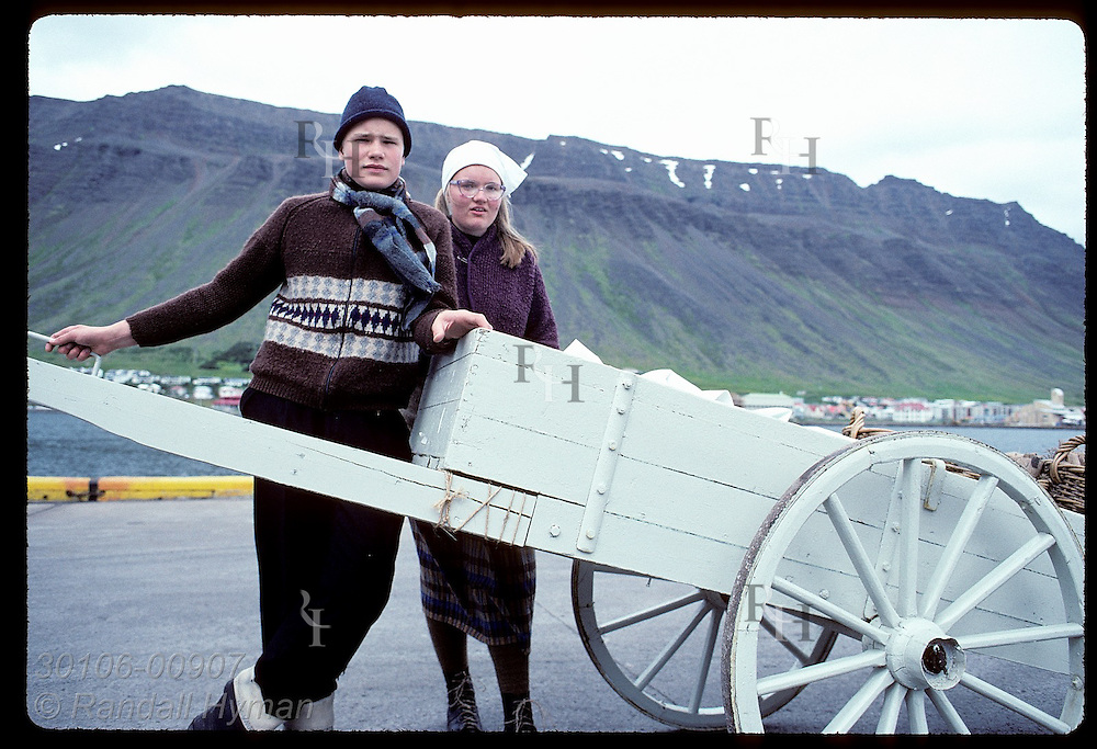 Teenage boy and girl pose by wagon from which they sell saltfish in town of Isafjordur. Iceland
