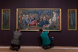 """© Licensed to London News Pictures. 22/10/2018. LONDON, UK. Staff members hang """"The Council Chamber"""", 1885-90, part of the Briar Rose series, by Edward Burne-Jones.  Preview of the largest Edward Burne-Jones retrospective to be held in a generation at Tate Britain.  Burne-Jones was a pioneer of the symbolist movement and the only Pre-Raphaelite to achieve world-wide recognition in his lifetime.  The exhibition runs 24 October to 24 February 2019.  Photo credit: Stephen Chung/LNP"""