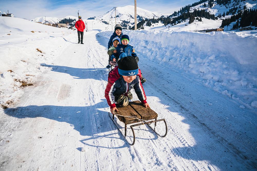 Kids sledding in the streets of Jyrgalan, Kyrgyzstan.