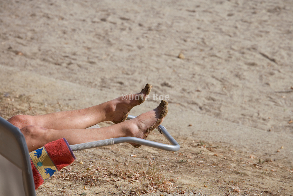 feet and legs of a person relaxing at a beach
