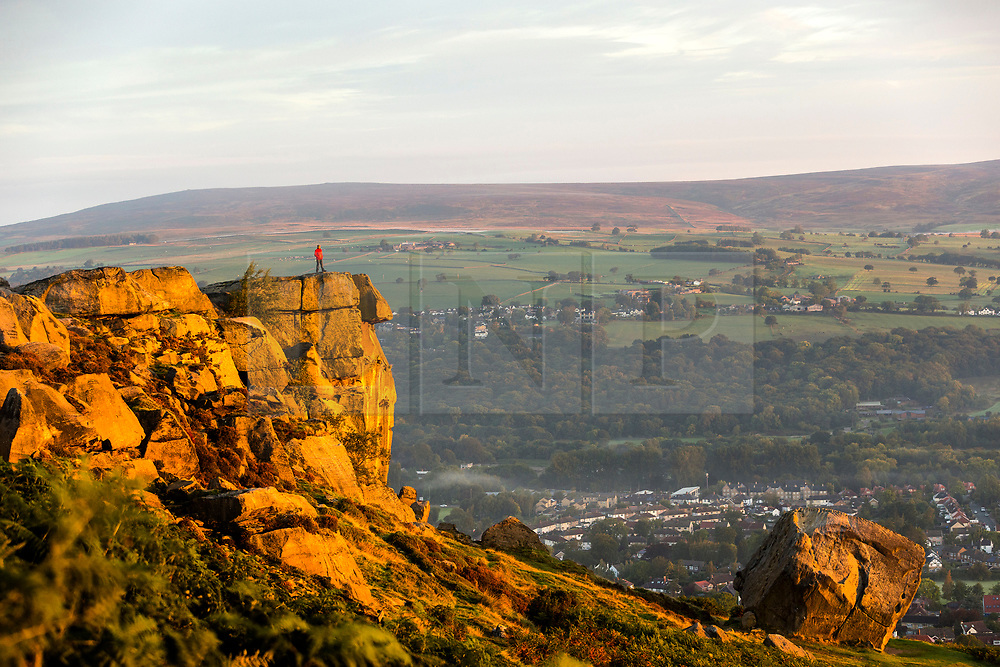 © Licensed to London News Pictures. 17/09/2018. Ilkley UK. The Cow & Calf rocks that sit 1,319ft above the town of Ilkley glow orange this morning as they are light up by the rising sun on a calm bright morning ahead of Storm Helene that is expected to hit Britain in the coming days. Photo credit: Andrew McCaren/LNP