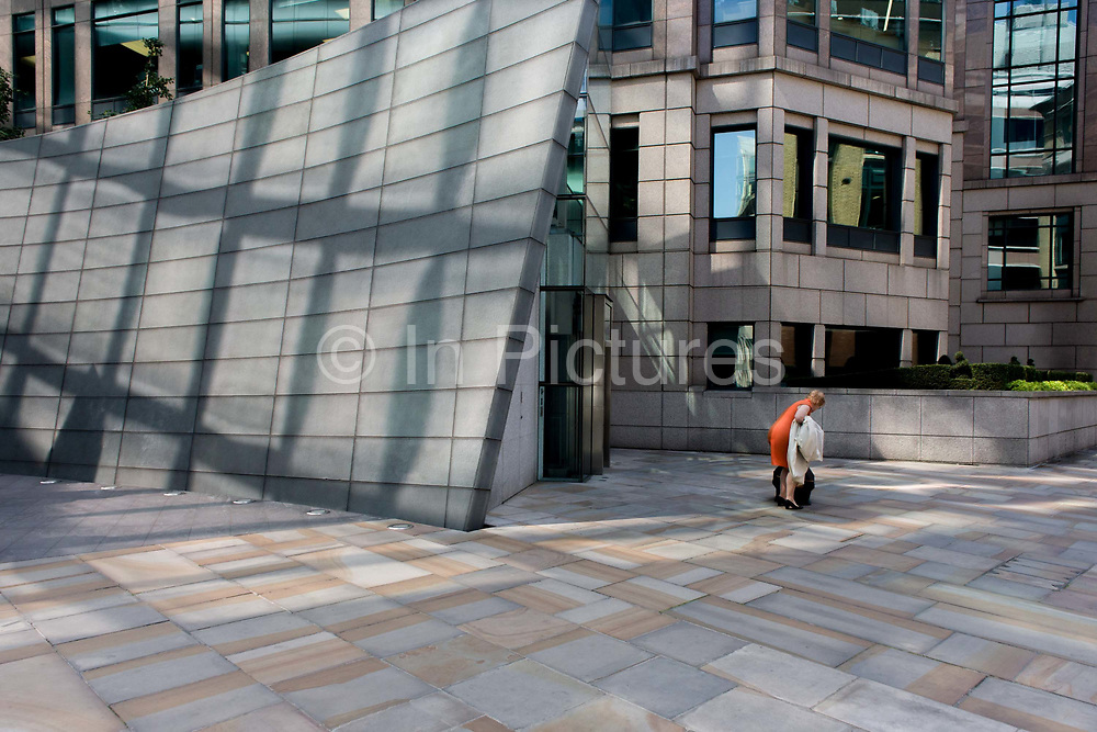 1980s architecture at the Broadgate City of London development and stooping woman. The lady bends over her awkward load surrounded by light reflections forming a chequered pattern on pavement and wall architecture. Office buildings are everywhere in the background. Broadgate Estate is a large, 32 acre (129,000 m²) office and retail estate in the City of London, owned by British Land and managed by Broadgate Estates. It was originally built by Rosehaugh and was the largest office development in London until the arrival of Canary Wharf in the early 1990s. The City is a major business and financial centre. Throughout the 19th century, the City was perhaps the world's primary business centre, and it continues to be a major meeting point for businesses