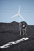 Eric Ross stands proudly with a mock wind turbine on top of the large coal mound at the Valmont Power Plant in Boulder, Colorado on April 27, 2010. During the protest for more renewables, Ross and three other climate activists claimed the coal mound for over an hour before being arrested for trespass.