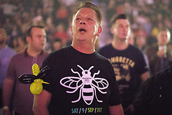 © Licensed to London News Pictures . 09/09/2017. Manchester , UK . A man with a Manchester Bee balloon animal on his arm and t-shirt from the event in the audience . We Are Manchester reopening charity concert at the Manchester Arena with performances by Manchester artists including  Noel Gallagher , Courteeners , Blossoms and the poet Tony Walsh . The Arena has been closed since 22nd May 2017 , after Salman Abedi's terrorist attack at an Ariana Grande concert killed 22 and injured 250 . Money raised will go towards the victims of the bombing . Photo credit: Joel Goodman/LNP