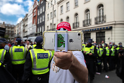 "© Licensed to London News Pictures. 10/06/2018. London, UK. A man with a Pepe the Frog mobile phone and a "" Make Britain Great Again "" baseball cap , videos photographers during the annual Al Quds day march in support of the Palestinian cause, in central London. Photo credit: Joel Goodman/LNP"