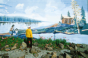 Alaska. Fairbanks. A tourist sightseeing admires a mural painting on a building downtown. MR.