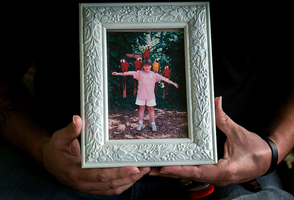 Sean Smith, 36, holds a family photo of his deceased younger sister, Erin Smith. Erin was accidentally shot and killed by Sean after he discovered a loaded gun while searching his parents' dresser for confiscated video games in June 1989. It was the first in a wave of shootings that week in Florida that sparked changes in the state's gun safety laws.