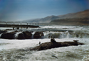 CS00963-12. Indians preparing Celilo fishing grounds for the beginning of the summer season. They are laying wires for the cable cars from the Oregon shore to Standing Island. The man is standing on Chinook Rock which is still mostly submerged in the spring high water. 1940s.