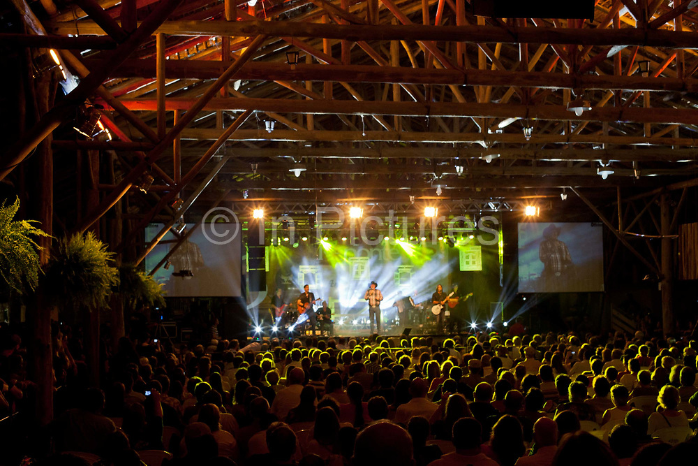 Crowd shot of medium to large music event, view from rear with smoke and lighting on stage, country music, famous Brazilian country singer Sergio Reys on stage. Reponte da Cancao music festival and song competition in Sao Lorenzo do Sul, RIo Grande do Sul, Brazil.
