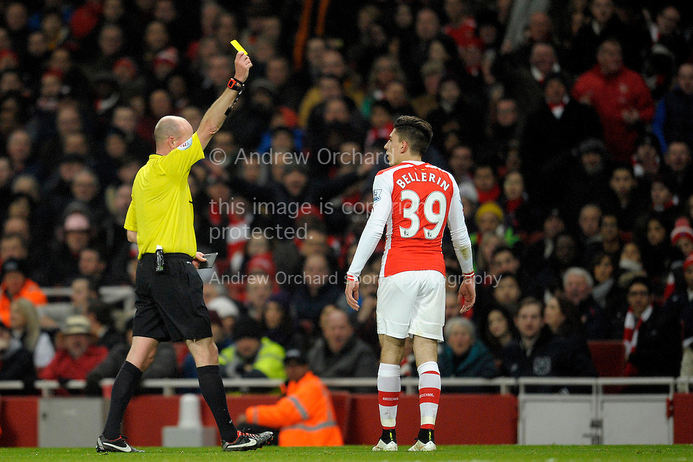 Match Referee Lee Mason giving a yellow card to Hector Bellerin of Arsenal after a foul on Paul Dummett of Newcastle United. Barclays Premier league match, Arsenal v Newcastle Utd at the Emirates Stadium in London on Saturday 13th December 2014.<br /> pic by John Patrick Fletcher, Andrew Orchard sports photography.