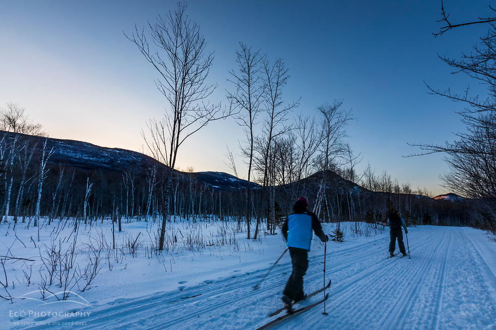 Two men cross-country skiing at dusk in Maine's Katahdin Woods and Waters National Monument.