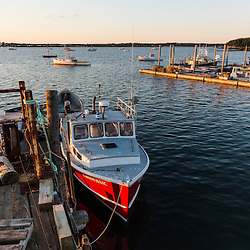 A lobster boat at a dock at Great Wass Lobster in Beals, Maine. The town dock is on the right.