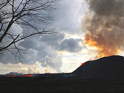 June 14, 2018 - Hawaii, U.S. - The Fissure 8 viewed from the north at 7:50 AM. The cone is roughly 50 m (165 ft) high at is peak, and a plume of sulfur dioxide and other volcanic gases rises as an orange tinge from the erupting lava fountains (hidden within the cone). Lava is still flowing out of the vent unabated as a full channel. To the left of the cone, a standing wave of lava can be seen in the channel. (Credit Image: © USGS/ZUMA Wire/ZUMAPRESS.com)