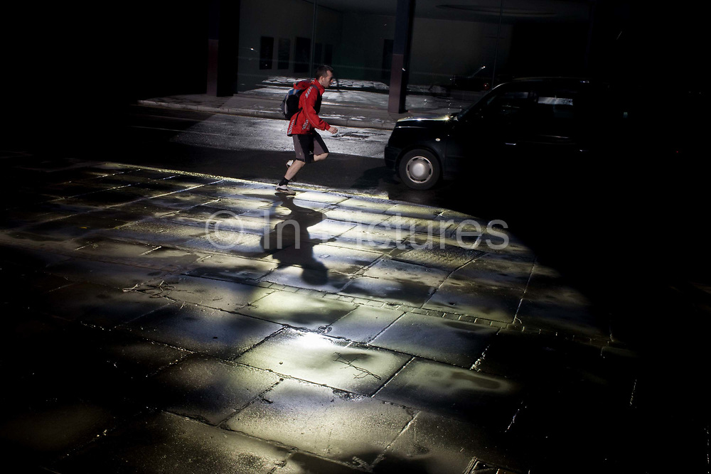 A runner passes-by a pool of bright reflective light in the heart of the financial City of London, known as the Square Mile after its ancient Roman walled past. Jogging through the pool of shining pavement, the man dressed in red with a rucksack on his back, he races through Royal Exchange Buildings in EC2, the heart of the capital's financial district, known as the Square Mile after its ancient Roman walled city.