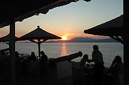 Sunset at the Sunset Cafe on  the island of Hydra, Greece. Photograph by Dennis Brack