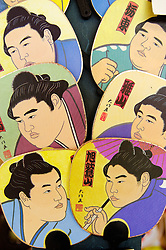 Souvenir fans with famous sumo wrestlers as design on sale at Sumo tournament in Japan
