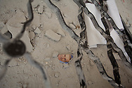 Amongst the destroyed ruins of the school in Lejj, Idlib lies a torn photograph of former president Hafez al-Assad, father of Bashar al-Assad, ripped from a school book. Lejj, Idlib, Syria. 16/06/2012