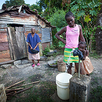 Juliana Luidenar collects water from the standpipe in her community, Batey Carmona, Dominican Republic. Water comes every three days. <br /> <br /> ACT Alliance member Servicio Social de Iglesias Dominicanas works with the community on water, sanitation and food production.