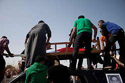 © under license to London News Pictures.  18/02/2011. People lift the body of Ali Al Almoumen off the car carrying him to the cemetary. Almoumen was third person to be buried in Sitra today after he was killed on Wednesday at the Pearl Roundabout.  Photo credit should read Michael Graae/London News Pictures