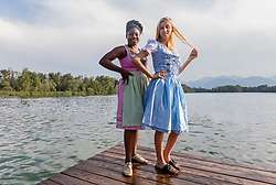 Teenage friends standing on pier over lake, Bavaria, Germany