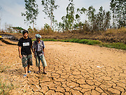 02 APRIL 2016 - NA SAK, LAMPANG, THAILAND:  A 79 year old farmer and his grandson walk through the water tank the farmer built for his water buffalo in Sobjant village. He said this is the first time the tank has been empty, and that in 2015, also a year of drought, he still had 1.5 meters of water in his tank at this time of year. The village of Sobjant in Na Sak district in Lampang province was submerged when the Mae Chang Reservoir was created in the 1980s. The village was relocated to higher ground a few kilometers from its original site.    PHOTO BY JACK KURTZ